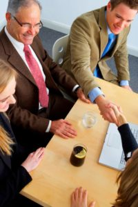 People shaking hands at a conference table talking about business insurance